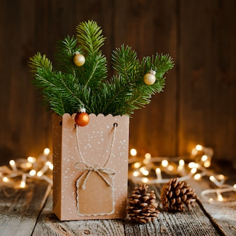 Christmas composition. paper bag with and bumps fir branches on brown wooden