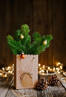 クリスマス作曲。茶色の木の表面とボケライトにバンプモミの枝が付いた紙袋。