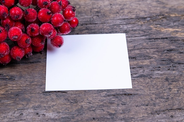 Christmas composition. paper blank with rowan hawthorn branch with berries on a wooden background