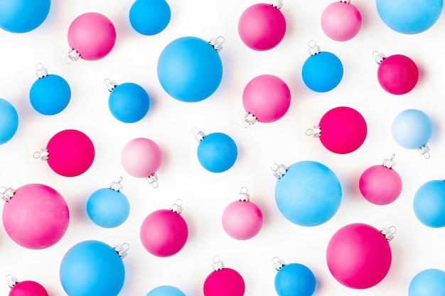 Новогодняя композиция. узор из синих и розовых новогодних шаров на белом фоне. плоская планировка, вид сверху