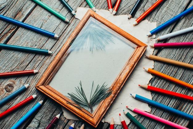 크리스마스 구성, 나무 탁자 위의 사진 프레임, 다양한 색상의 연필 주위에 나무 가지가 흩어져 있습니다.
