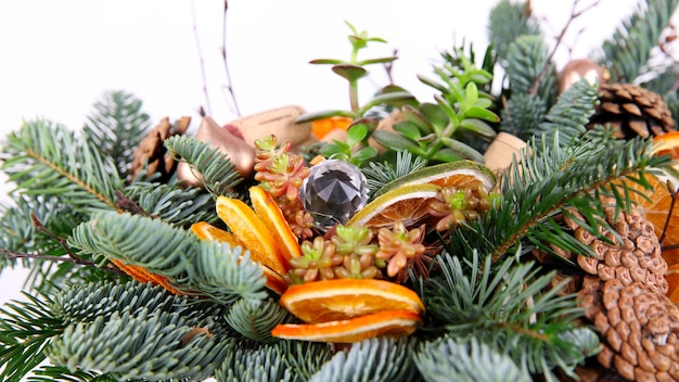 Christmas composition of pine branches, wine corks, balls, dried orange slices and pine cones. close up shot. selective focus. on white background