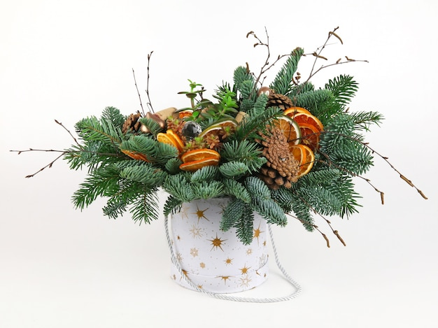Christmas composition of pine branches, wine corks, balls, dried orange slices and pine cones. in white bucket. on white background