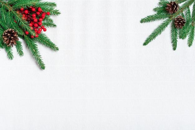 クリスマスの組成物。松ぼっくり、紙の白い背景の上のモミの枝。フラット横たわっていた、トップビュー、コピースペース。