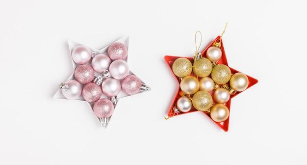 Новогодняя композиция. розовые и серебряные новогодние шары, выложенные в форме звезды на белом фоне.