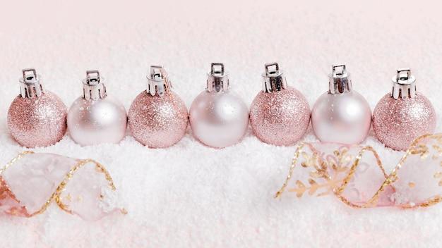 Новогодняя композиция. розовые и серебряные новогодние шары на снежно-белом фоне.