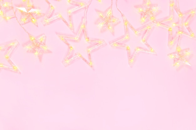 Christmas composition on a pink background. frame of garland star. christmas concept. flat lay, top view and copy space