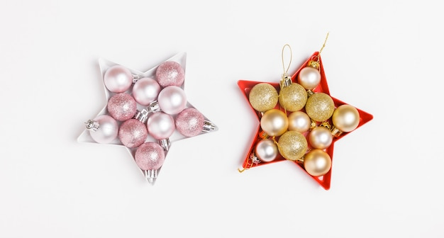 Christmas composition. pink and silver christmas balls laid out in the shape of a star on white background.