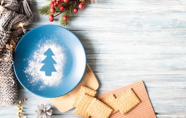 クリスマスの構成、プレート、クッキー、木製の背景にクリスマスの装飾