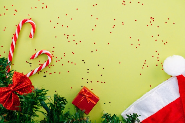 Christmas composition. present box, firtree branches, xmas candies, red festive decorations on green background. copy space.