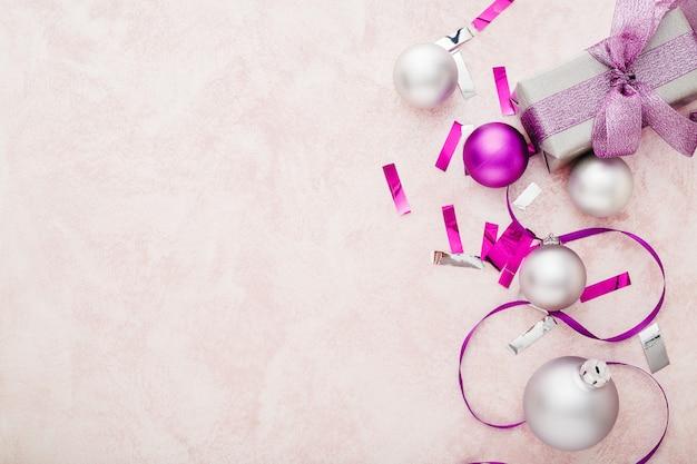 クリスマスの構成紫と銀のお祝いの装飾のリボン、ピンクの背景にボール。コピースペース