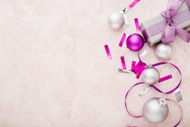 Christmas composition purple and silver festive decor ribbons,balls on pink background. copy space
