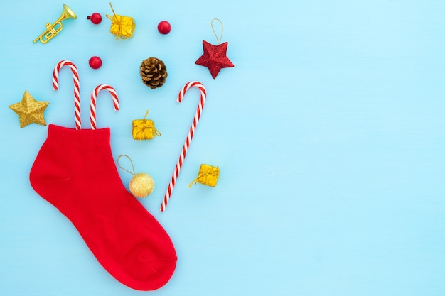 Christmas composition.  red christmas stocking with decoration on blue background.
