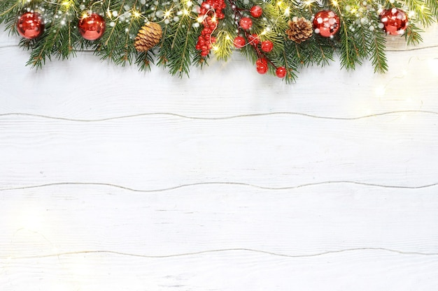 Christmas composition of red decoration with fir branches on white wooden background