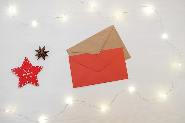 Christmas composition. red decorations with letter envelope on white background.