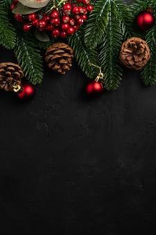 크리스마스 구성. 붉은 장식, 소나무 콘 및 전나무 바늘 장식 어두운 표면에. 상위 뷰 복사 공간