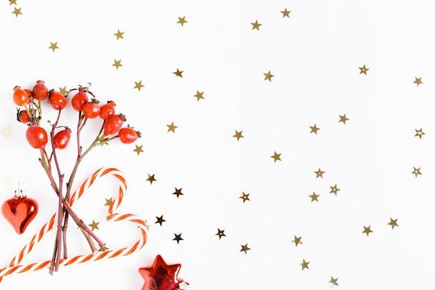 Новогодняя композиция. красные ягоды шиповника, рождественская конфета на белом фоне и золотые звезды. рождество, новый год, зимняя концепция. плоская планировка, вид сверху, копия пространства