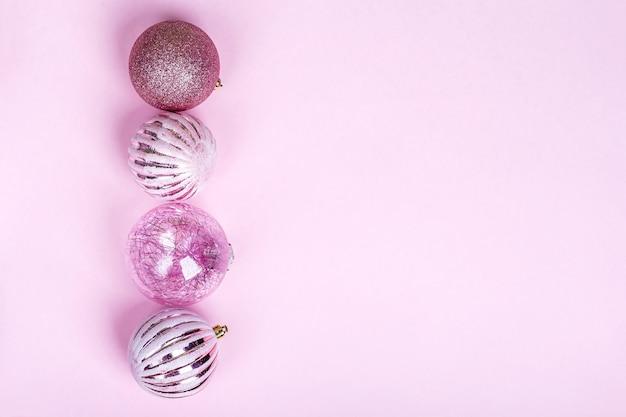 크리스마스 구성. 핑크 크리스마스 장식, 파스텔 배경에 빛나는 공 세트