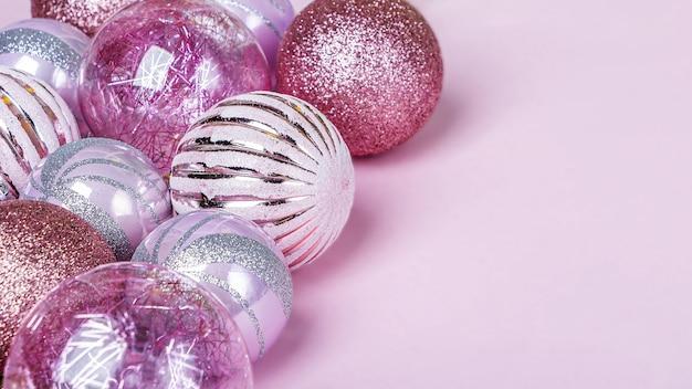 クリスマス作曲。クリスマスピンクの装飾、パステル背景の光沢のあるボールのセット
