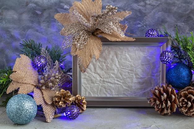Рождественская композиция серебристо-синего цвета новогоднее украшение рамка на сером фоне копией пространства