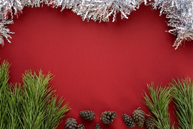 Новогодняя композиция. еловые ветки и шишки с белой мишурой на красном фоне. плоская планировка, вид сверху, место для текста