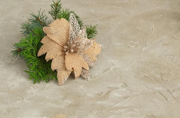 Новогодняя композиция еловые ветки декоративный рождественский цветок на бетонном фоне копией пространства