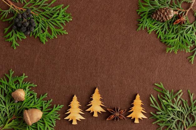 茶色のフェルトの背景のコピースペースに鹿の置物とクリスマスの構成トウヒの枝