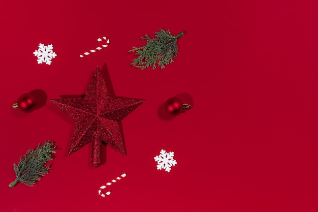 Christmas composition star balls branches of a christmas tree snowflakes candies on a red background