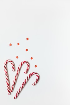 Christmas composition three caramel candy canes, confetti stars on white background with copy space.