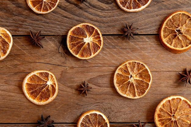 크리스마스 구성입니다. 나무 배경에 마른 오렌지와 스타 아니스의 평면 배치. 소박한 휴일 향신료 재료