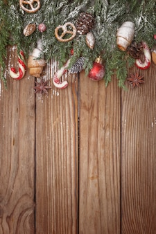 Christmas composition of tree branches, candies and decorations on wooden background. top view. copy space.