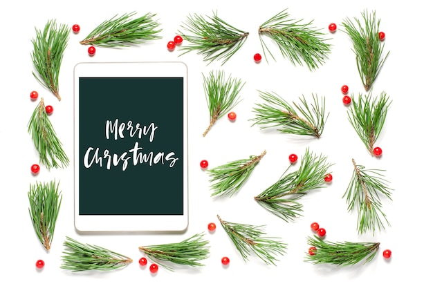Christmas composition on a white background. merry christmas-handwritten inscription on the gadget screen. flat lay.