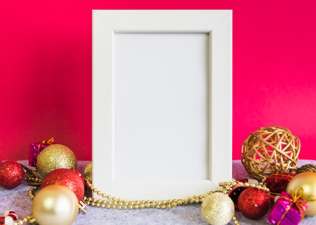 Christmas composition of white frame with baubles on table