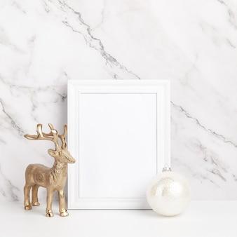 クリスマスの作文。大理石の背景に白いフレームのクリスマスの装飾とギフト