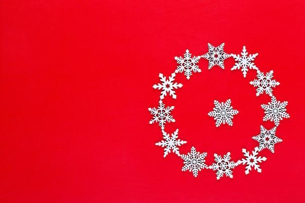 Новогодняя композиция. белый снег хлопья венок украшения на красном фоне. рождество, зима, новый год концепция. плоская планировка, вид сверху, копия.