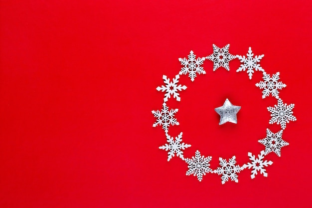 Новогодняя композиция. белый снег хлопья венок украшения на красном фоне. рождество, зима, новогодняя концепция. плоская планировка, вид сверху, копия.