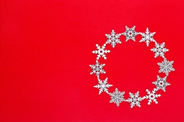Новогодняя композиция. белые снежные хлопья венок украшения на красном фоне. рождество, зима, новогодняя концепция. плоская планировка, вид сверху, копия.