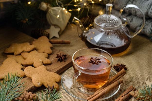 お祝いの装飾でお茶のティーポットとジンジャーブレッドのクッキーのカップとクリスマスの構成