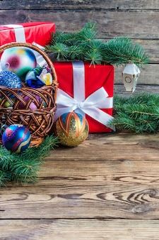 Christmas composition with balls and gifts on wooden table