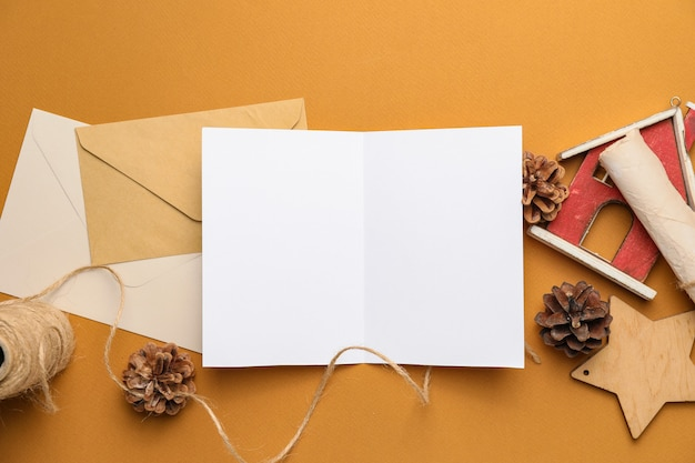 Christmas composition with blank card and envelopes on color background