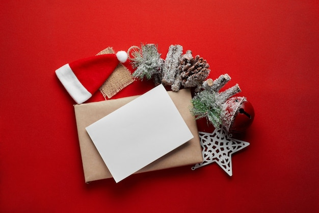 Christmas composition with blank greeting card over gift box made of kraft paper with santa hat