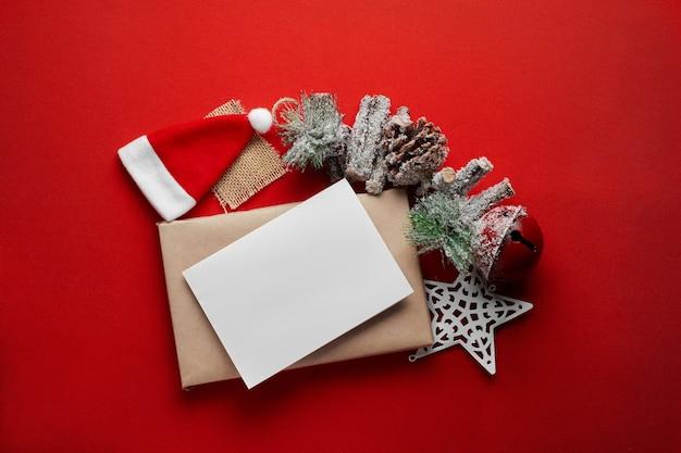 サンタの帽子とクラフト紙で作られたギフトボックスの上に空白のグリーティングカードとクリスマスの構成