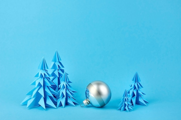 Christmas composition with blue paper fir trees and silver ball