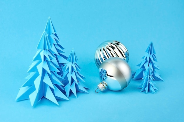 Christmas composition with blue paper fir trees and silver balls