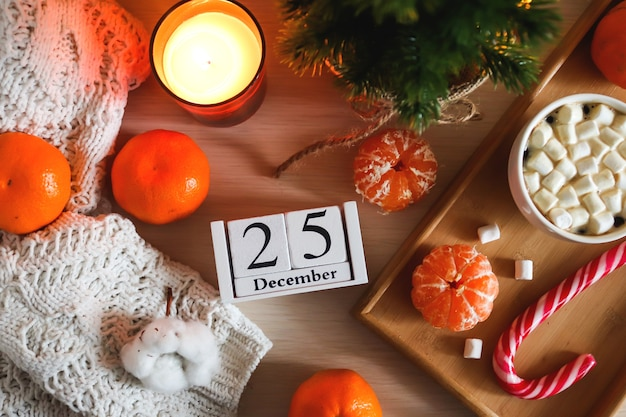 カレンダーの日付とクリスマスの構成12月のキャンドルクリスマスツリーとみかん