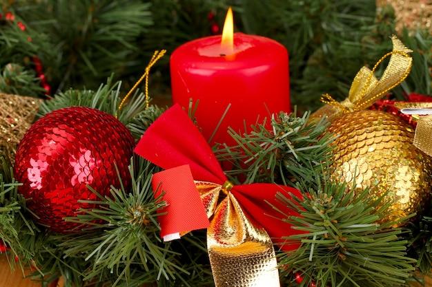 촛불과 나무 표면에 빨간색과 금색 색상으로 장식 된 크리스마스 구성