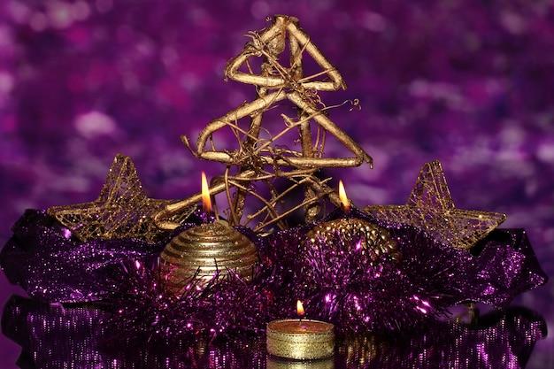 Новогодняя композиция со свечами и украшениями в фиолетовых и золотых тонах на яркой поверхности