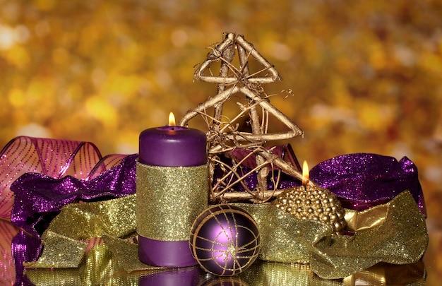 Новогодняя композиция со свечами и украшениями в фиолетовых и золотых тонах