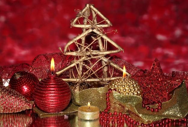 Новогодняя композиция со свечами и украшениями в красных и золотых тонах на яркой поверхности