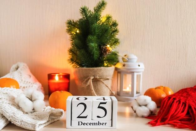 キャンドルランタンとクリスマスの構成クリスマスツリーカレンダーニットセーターと格子縞
